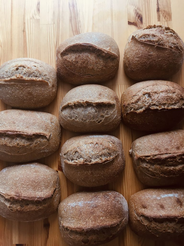Eleven loaves on a wooden table. Clear oven spring can be observed.