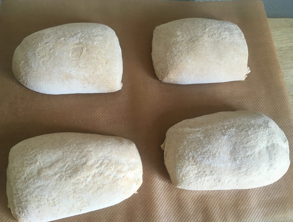 4 pieces of dough transferred from bakers linen to baking sheets. There's some undesired variation in shape.